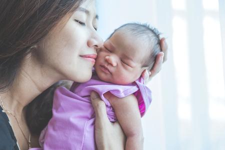 Een portret van een jonge moeder die haar pasgeboren baby houdt, glimlacht gelukkig