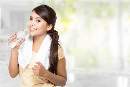 deporte: Un retrato de una joven y bella mujer asiática beber agua mineral después de hacer ejercicio