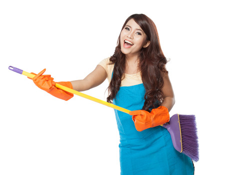 woman holding sign: A portrait of a beautiful young asian woman holding a broom, use it like a guitar while smiling to the camera
