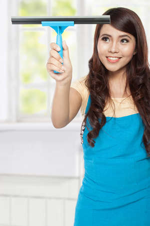 domestic chores: A portrait of a beautiful young asian woman doing domestic chores