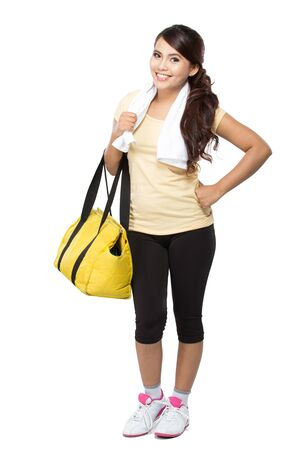 woman bag: A portrait of a happy fit young woman with gym bag standing ready for fitness exercise Stock Photo