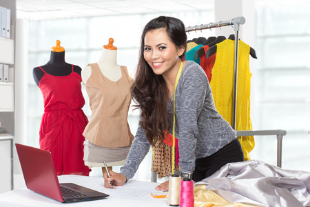 hanged woman: A portrait of a young asian designer woman using a laptop and smiling,clothes hanged as background Stock Photo
