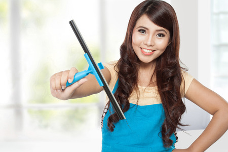 clear water: A portrait of a Beautiful young asian women doing domestic chores using glass cleaning wiper