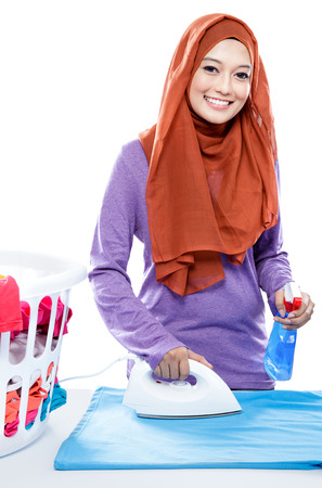 hijab: portrait of young woman wearing hijab ironing clothes and spraying perfume isolated on white Stock Photo