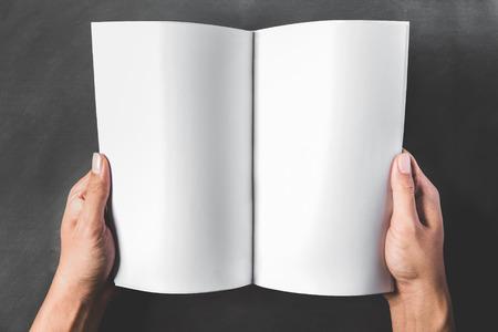 open book: cerca retrato de manos que sostienen un libro abierto con p�ginas en blanco sobre fondo oscuro