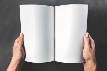 business book: close up portrait of hands holding an open book with blank page on dark background