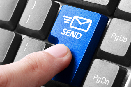 Sending email. gesture of finger pressing send button on a computer keyboard