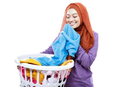 portrait of young woman wearing hijab carrying laundry basket while smelling fresh clean clothes isolated on white Foto de archivo