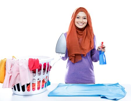 perfume spray: portrait of young woman wearing hijab jolding iron and perfume spray isolated on white
