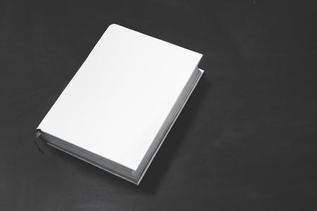 コピー領域と背景の黒のボードの白いカバーの厚い本の肖像画