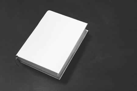 books: portrait of thick book with white cover on black board for background with copy space