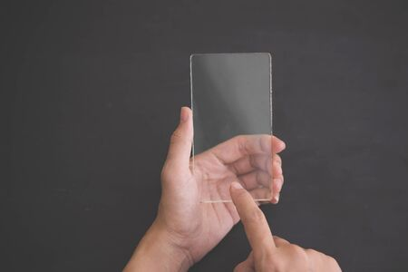 futuristic background: A portrait of a blank glass square on black background, futuristic transparent smart phone mock up Stock Photo
