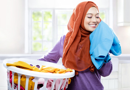 casual clothing: portait of young woman wearing hijab carrying laundry basket while smelling fresh clean clothes Stock Photo