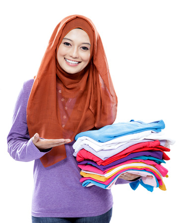 portrait of young woman smiling and presenting clean clothes after ironing isolated on white background