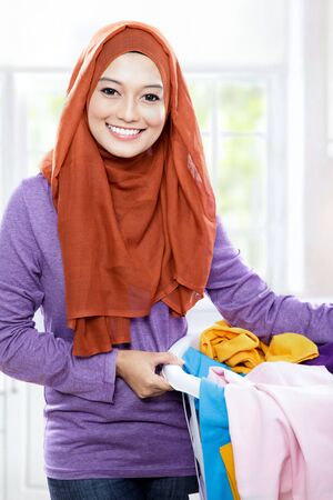 household tasks: close up portrait of beautiful smiling woman wearing hijab holding a laundry basket