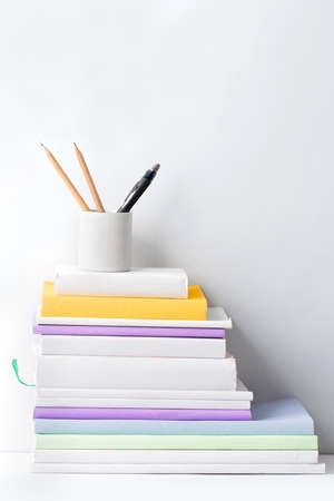 desk tidy: portrait of stack of books and stationery in glass on white background with copy space Stock Photo