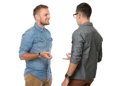 personas hablando: retrato de dos hombres jóvenes hablando entre sí, aislado sobre fondo blanco Foto de archivo