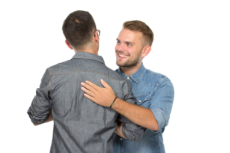 happy people white background: portrait of two young  man greeting patting each other, isolated over white background Stock Photo