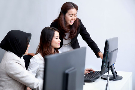 happy work: portrait of businesswomen telling information to her co-worker at office