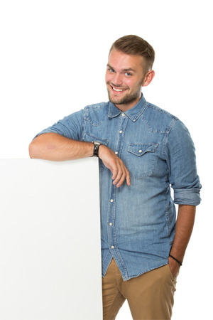 hoja en blanco: portrait of young  man smiling next to a blank white billboard, isolated. ready for your design Foto de archivo