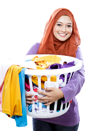 dirty clothes: portrait of housewife wearing hijab carrying laundry basket full of dirty clothes isolated on white background