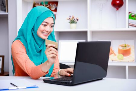shop online: portrait of beautiful young muslim woman browsing internet on laptop while holding a credit card at living room