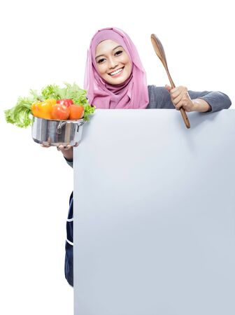 hold on: portrait of young smiling woman carrying a pan full of vegetables and wooden spatula with hands on white board