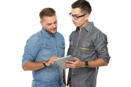 portrait of two young  man discussing over a tablet pc, isolated over white background