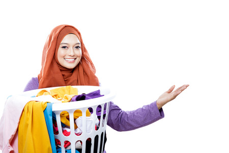 close up portrait of housewife wearing hijab carrying laundry basket full of dirty clothes and presenting copy space isolated on white 版權商用圖片