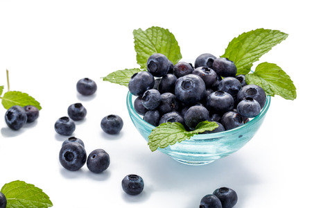 fresh blueberries and mint leaves in a glass bowl on white background