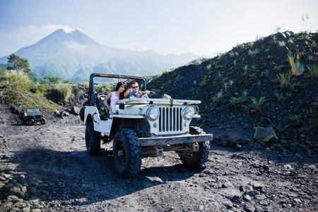 Un retrato de raza mixta pareja haciendo alguna aventura de montar una carretera jeep.