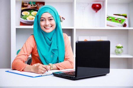 portrait of beautiful muslim woman writing an information from laptop at office
