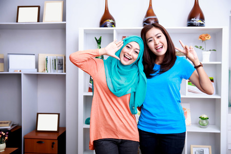 portrait of two cheerful women posing in front of camera at decorated living room Stock Photo