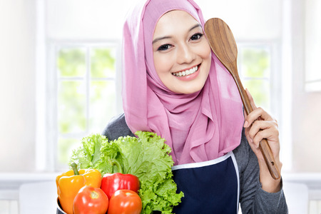 young woman smiling: close up portrait of young smiling woman carrying a pan full of vegetables and wooden spatula in the kitchen Stock Photo