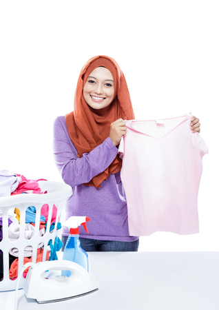 'pick up': portrait of young woman wearing hijab ironing while pick up a clothes isolated on white background