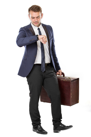 looking at watch: portrait of Businessman holding a suitcase while looking at his watch. ready for your design