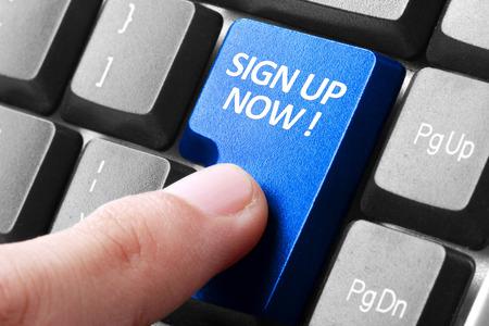 La firma para arriba. gesto de dedo que presiona Registrarse ahora botón en un teclado de computadora