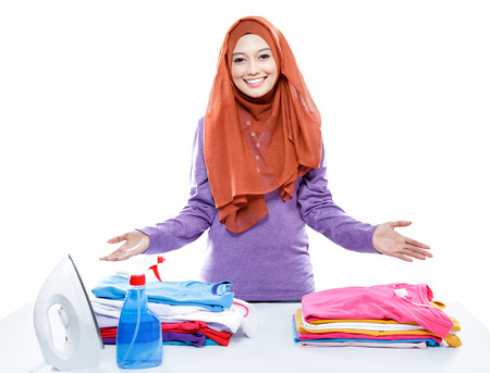 tidy: portrait of young woman wearing hijab presenting clean and tidy clothes after ironing isolated on white
