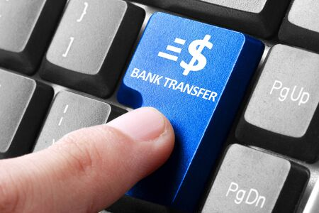 transfering: Transfering online. gesture of finger pressing Bank Transfer button on a computer keyboard Stock Photo