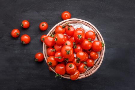 jitomates: vista superior completa de la pila de tomates cherry en una cesta de mimbre a bordo negro para el fondo Foto de archivo