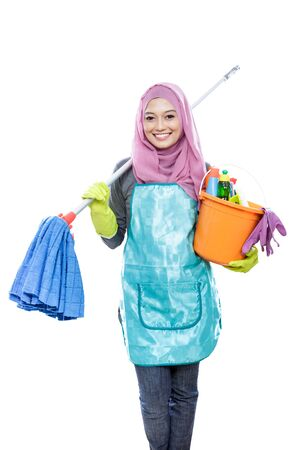 house maid: portrait of cheerful housewife wearing hijab holding mop and carrying a bucket full of cleaning supplies isolated on white