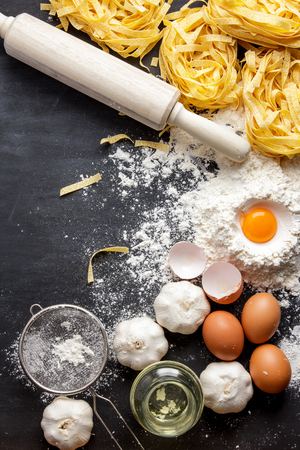 italian homemade fettucine and ingredients on black board with copy space Stock Photo