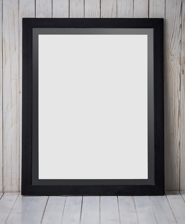 canvas on wall: A portrait of a Black frame placed vertically on wooden background, mock up