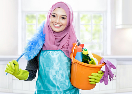 house maid: portrait of smiling cleaner young woman wearing hijab