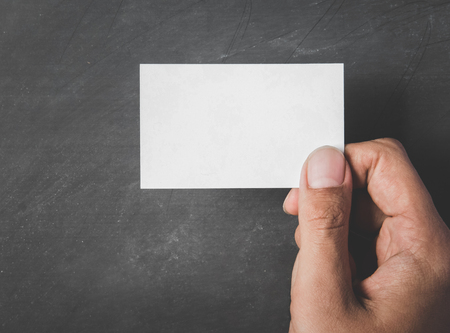 contact sheet: close up portrait of hands holding blank business card with black board for background Stock Photo