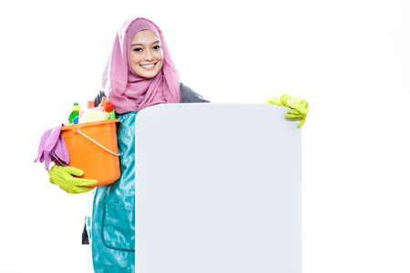 hijab: portrait of young woman wearing hijab holding a bucket full of cleaning supplies with white board isolated on white background