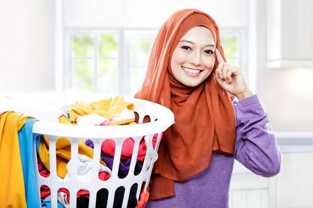 niña pensando: retrato de la hermosa mujer que lleva velo que lleva la cesta de lavado con la mano en sus cabezas pretende pensamiento