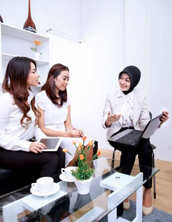 presenting: portrait of three businesswomen meeting at office living room with copyspace