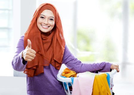ランドリー バスケットを運ぶと親指をあきらめてヒジャーブを着ている美しい笑顔の女性の肖像画 写真素材