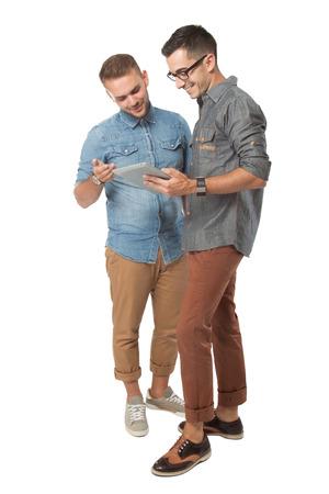 portret van twee jonge man op zoek naar een tablet-pc, die over een witte achtergrond
